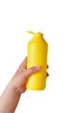 Hand holding yellow plastic bottle isolated on white background Royalty Free Stock Images