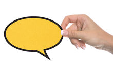 Hand holding a yellow speech bubble symbol Royalty Free Stock Photography
