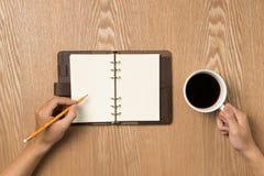 hand holdingillustrationmanlign min originella målade penna Tabell med den öppna notepaden Kupa av kaffe Arkivfoto