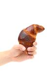 Hand holds appetizing croissant. Royalty Free Stock Images