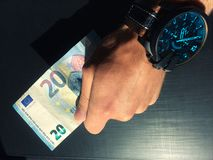 Hand holds a bank note, keep money, money in the palm of your hand, receive money, give money, watch on hand, Europea royalty free stock image