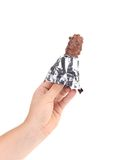 Hand holds bar chocolate in foil. Stock Images