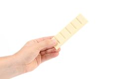 Hand holds bar of white chocolate. Stock Photos
