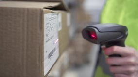 Hand holds a barcode scanner in the warehouse