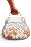 The hand holds a basket with eggs on the white.  Stock Photos