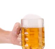 Hand holds big mug with gold beer. Stock Photography