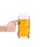 Hand holds big mug with gold beer. Royalty Free Stock Images