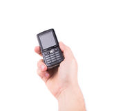 Hand holds black cell phone. Isolated on a white background Stock Images