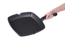 Hand holds a black frying grill pan Stock Photos