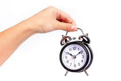 Hand holds a black shiny alarm clock on white background.  Stock Photo