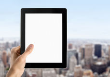 Hand Holds Blank Tablet PC. Man hands are holding touch screen device with blank screen. Blurred cityscape with skyscrapers on background Royalty Free Stock Photography