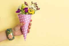 Flowers in a horn for ice cream popart. Hand holds a bouquets of flowers in a paper horn with hearts on a yellow background. a gift for St. Valentine& x27;s Day royalty free stock photography