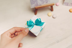Hand holds bow of blue gift on wooden table Royalty Free Stock Images