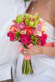 Hand holds bridal bouquet