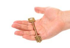 Hand holds bronze steel key. White background stock photos