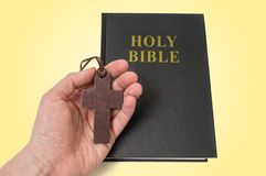 Hand holds brown crucifix on necklace and holy bible in background Stock Photos