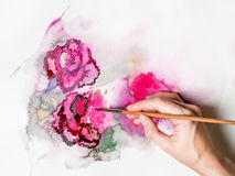 The hand holds the brush paints with watercolor. Abstract flowers Royalty Free Stock Photos
