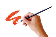 Hand holds the brush with red paint Stock Image