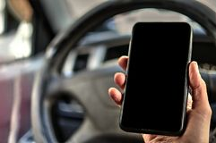 Hand holds the cell phone. Against the background of the steering wheel of the car. Phone with a blank black screen for an inscription or picture royalty free stock images