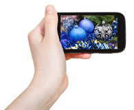 Hand holds cellphone with Xmas decorations Royalty Free Stock Photos