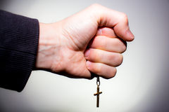 Hand holds a chain with gold crucifix. Isolated on white stock image