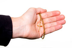 Hand holds a chain with gold crucifix Stock Photo