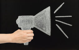 Hand holds chalk megaphone drawn on blackboard Stock Image