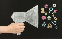 Hand holds chalk megaphone with flying icons. Drawn on blackboard by hand not in photoshop Stock Photography