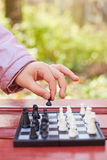 Hand holds chess piece above chessboard while game Royalty Free Stock Image