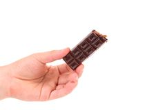 Hand holds chocolate bar with filling. Royalty Free Stock Image