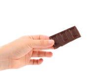 Hand holds chocolate bar. Stock Photo