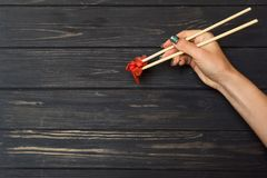 Hand holds chopsticks with ginger Royalty Free Stock Photo