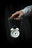 Hand holds a clock, hanging on cords, and manages it Stock Image