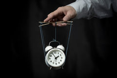 Hand holds a clock, hanging on cords, and manages it Stock Photo