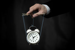 Hand holds a clock, hanging on cords, and manages it Stock Photos