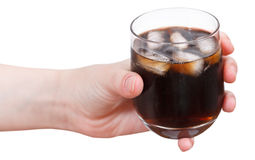 Hand holds cola with ice in glass isolated Stock Photo