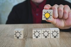 A hand holds a cube with a burning lamp when all the other lamps are extinguished, which symbolizes the New Idea, the concepts of stock photos