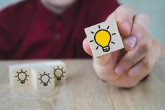 A hand holds a cube with a burning lamp when all the other lamps are extinguished, which symbolizes the New Idea, the concepts of royalty free stock photography