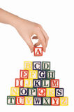 The hand holds a cube with letters stock photo