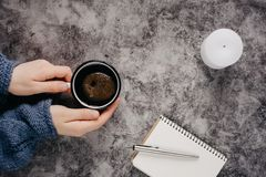 Hand holds cup of coffee on gray table with candle, notebook, pen royalty free stock photography