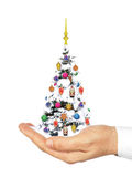 Hand holds a decorated Christmas tree in the snow. Royalty Free Stock Image