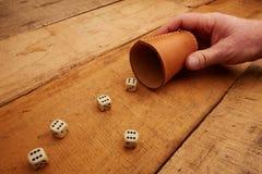 Hand holds the dice cup. Meinten Sie: Glücksspiel mit würfeln für Erfolg, Glück, Einsatzfreude Gambling with dice for success, happiness, enthusiasm stock photography