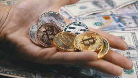 Hand Holds Different Coins of Cryptocurrency on a Table with US Dollars are Rotating. Crypto currency in Macro. Crypto Currency Close-up. Virtual money on stock video footage