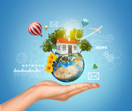 Hand holds Earth with house. Air balloons, Royalty Free Stock Image