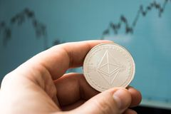 Hand holds ethereum coin. Concept image for curse of bitcoin crypto currency Stock Images