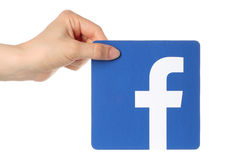Hand holds facebook logo. KIEV, UKRAINE - APRIL 30, 2015: Hand holds facebook logo printed on paper on white background. Facebook is a well-known social stock images