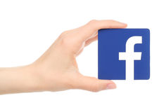 Hand holds facebook logo. Kiev, Ukraine - May 18, 2016: Hand holds facebook logo printed on paper on white background. Facebook is a well-known social networking stock photography