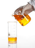 Hand holds flask to make a chemical reaction Royalty Free Stock Images