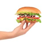 Hand holds french baguette sandwich. Royalty Free Stock Images