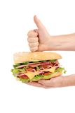 Hand holds french baguette sandwich. Isolated on a white background Royalty Free Stock Photography
